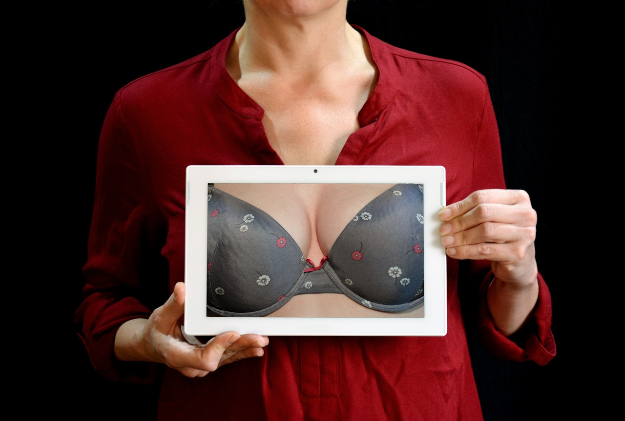 woman holding photo of close up of breasts and bra breast reconstruction concept