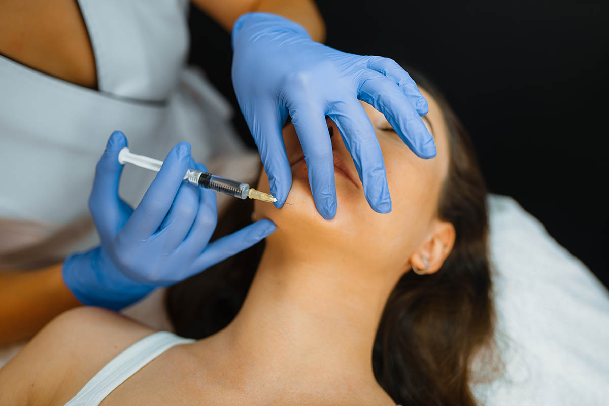 Cosmetician gives chin botox injection to patient