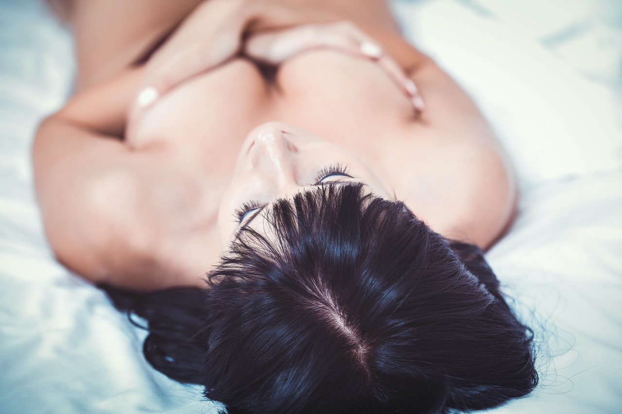 woman laying in bed with hands over her breasts